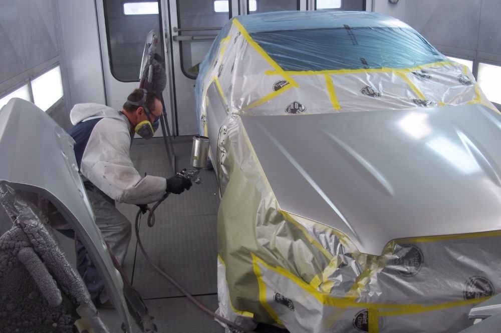 A man paints a car in a paint spraying booth.
