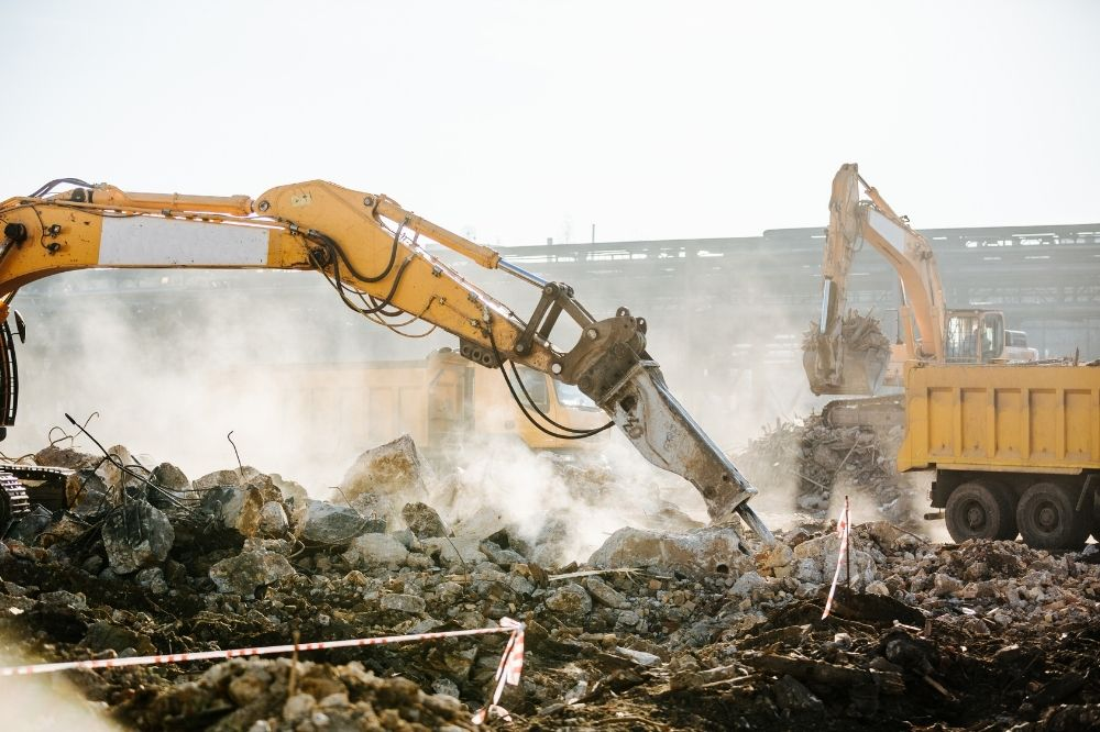 Photo of large construction equipment producing a dusty environment.