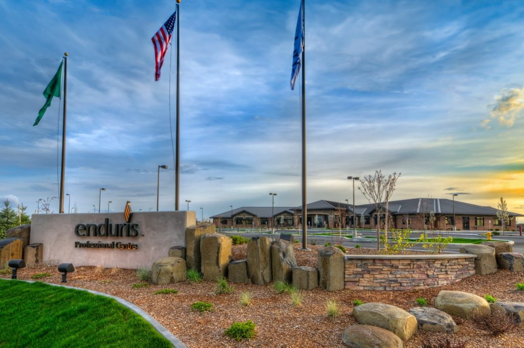Photo of the Enduris Spokane building with blue sky and three flags.